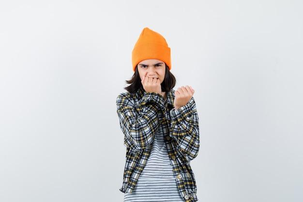 Portret van een jonge vrouw met een vuist op de mond in een oranje hoed die er nerveus uitziet?