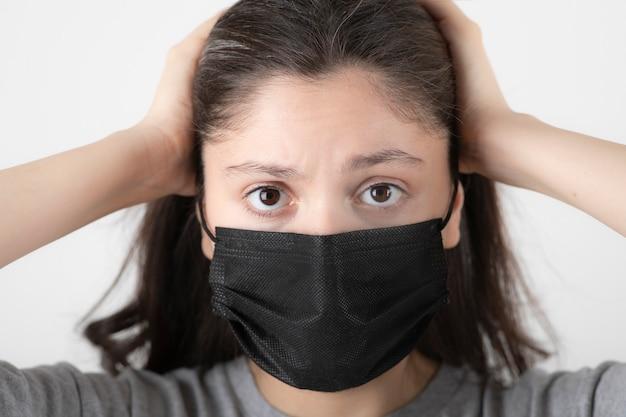 Portret van een jonge vrouw met een zwart gezichtsmasker die haar hoofd vasthoudt.