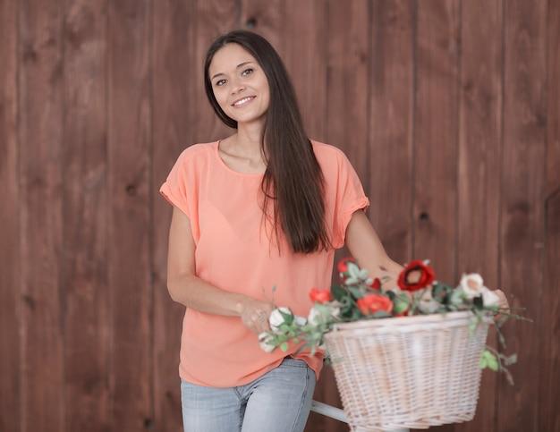 Portret van een jonge vrouw met fiets- en lentebloemen in een mand