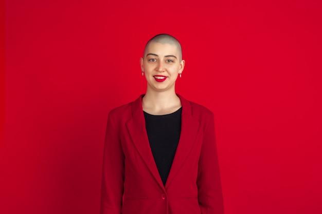 Portret van een jonge vrouw met freaky uiterlijk op rode muur