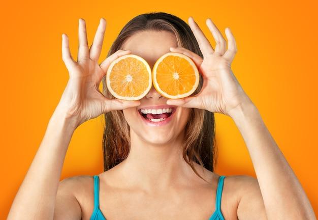 Portret van een jonge vrouw met gehalveerde sinaasappels voor haar ogen. menselijke gezichtsuitdrukkingen en emoties.