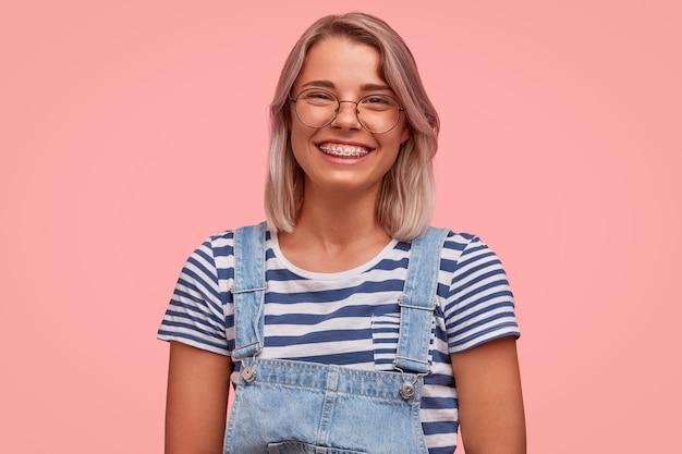 Portret van een jonge vrouw met gekleurd haar dat een overall draagt
