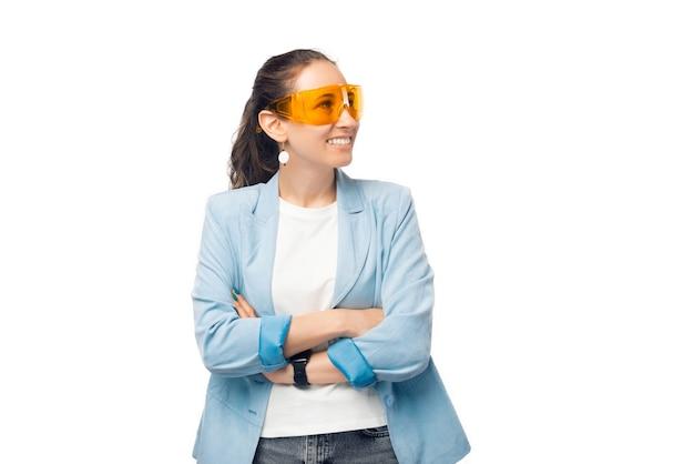 Portret van een jonge vrouw met gekruiste armen die opzij kijkt terwijl ze een oranje veiligheidsbril draagt.