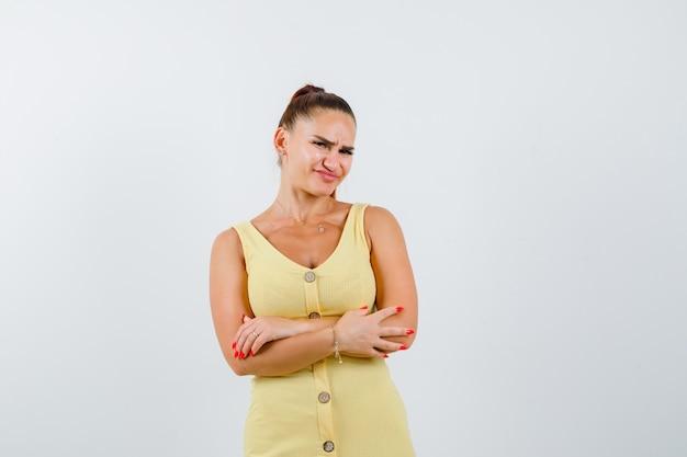 Portret van een jonge vrouw met gekruiste armen in gele jurk en op zoek naar ontevreden vooraanzicht