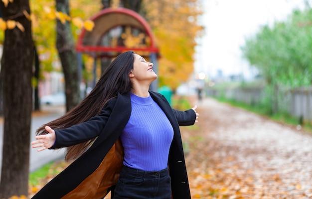 Portret van een jonge vrouw met geopende armen in herfst park