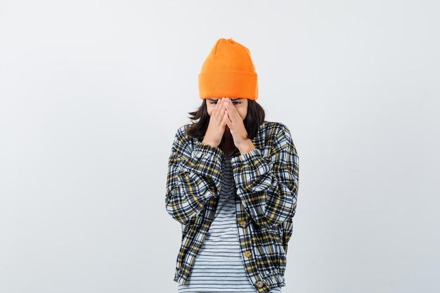 Portret van een jonge vrouw met gezicht met handpalmen in oranje hoed en geruit hemd