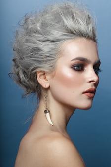 Portret van een jonge vrouw met grijs kapsel, smokey eyes en perfecte make-up met blote schouders, op blauwe achtergrond.