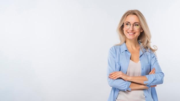 Portret van een jonge vrouw met haar gekruiste armen tegen een witte achtergrond
