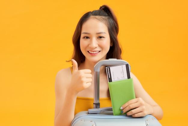 Portret van een jonge vrouw met haar paspoort en bagage over oranje muur