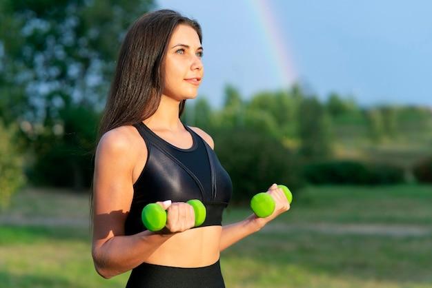 Portret van een jonge vrouw met halters in handen fitness sport in het park