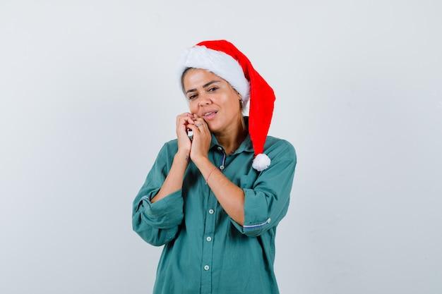 Portret van een jonge vrouw met handen in de buurt van mond in shirt, kerstmuts en charmant vooraanzicht