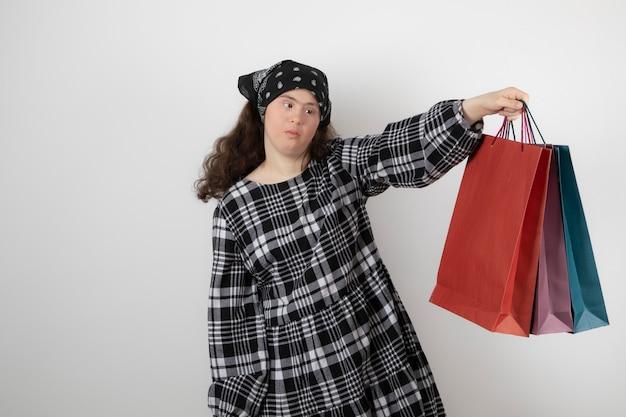 Portret van een jonge vrouw met het syndroom van down die een heleboel boodschappentas vasthoudt.