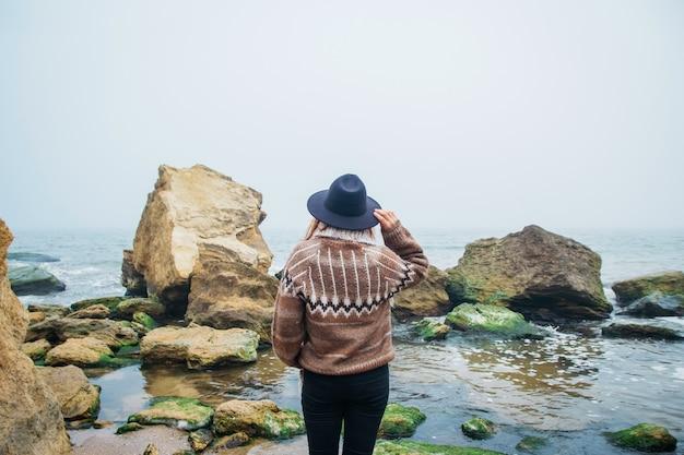 Portret van een jonge vrouw met hoed op een rots tegen een prachtige zee schieten vanaf de achterkant