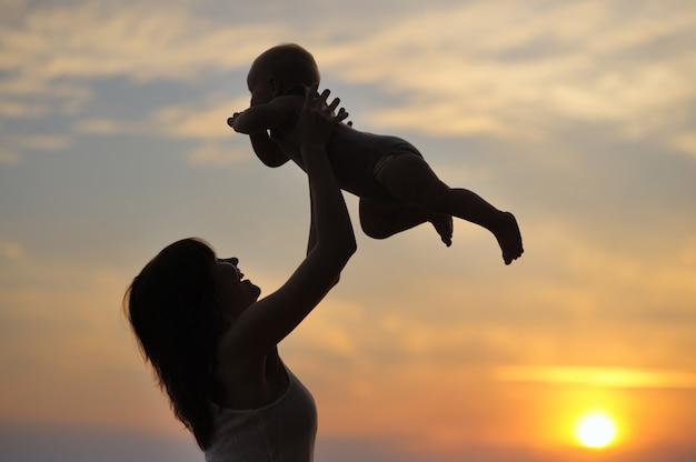 Portret van een jonge vrouw met kleine baby als silhouet aan het water