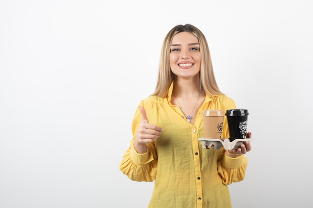 Portret van een jonge vrouw met kopjes koffie en duimen opgevend.