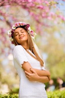 Portret van een jonge vrouw met krans van verse bloemen op het hoofd
