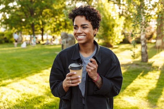 Portret van een jonge vrouw met krullend haar die afhaalkoffie vasthoudt en drinkt uit een papieren beker tijdens het wandelen in het stadspark
