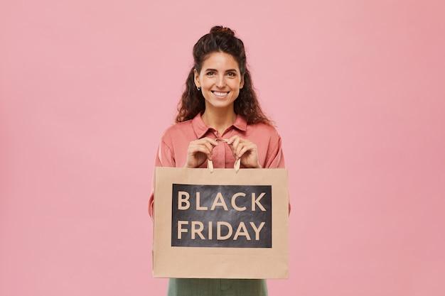 Portret van een jonge vrouw met krullend haar die lacht terwijl ze aankoop van black friday tegen de roze achtergrond vasthoudt
