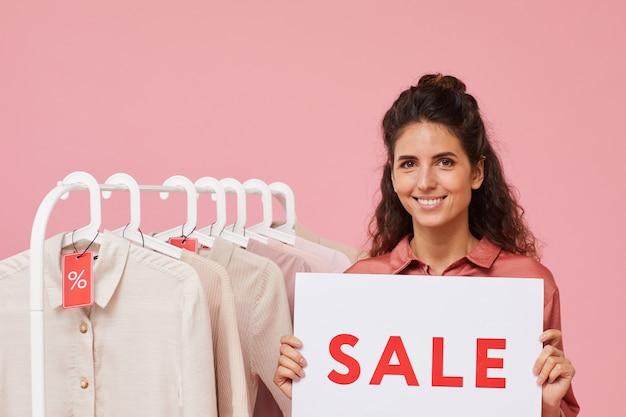 Portret van een jonge vrouw met krullend haar die teken met verkoop houden en bij camera glimlachen die zij kleren verkoopt