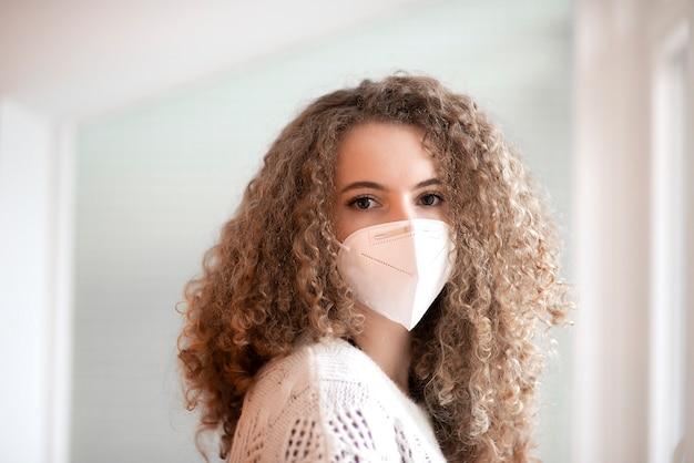 Portret van een jonge vrouw met krullend haar en droevige ogen in witte kleur medische beschermend gezichtsmasker op zoek naar camera
