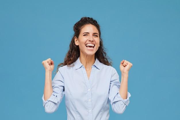 Portret van een jonge vrouw met krullend haar is blij met iets terwijl ze tegen de blauwe achtergrond staat