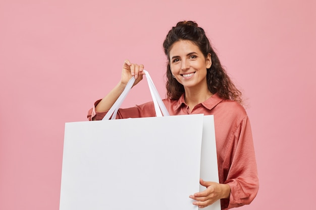 Portret van een jonge vrouw met krullend haar met grote boodschappentas en glimlachend in de camera tegen de roze achtergrond