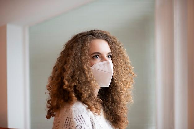 Portret van een jonge vrouw met krullende haren en droevige ogen in wit medisch beschermend gezichtsmasker venster kijken