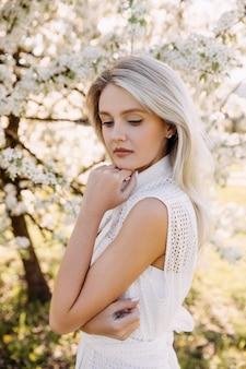 Portret van een jonge vrouw met lang blond haar buiten in een park