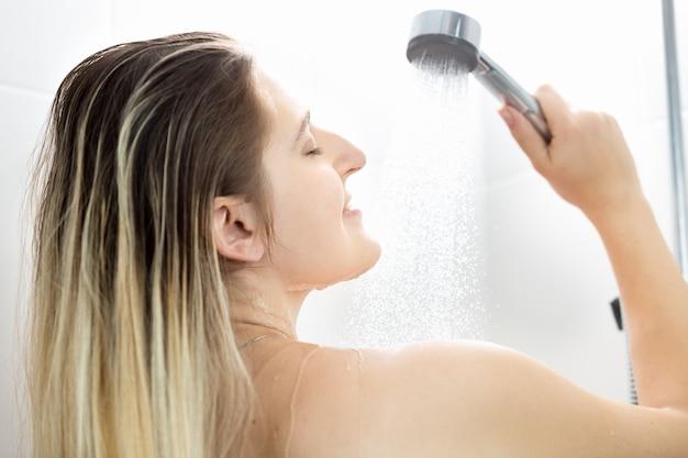 Portret van een jonge vrouw met lang blond haar die in de douche wast