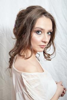 Portret van een jonge vrouw met lang golvend bruin haar en blote schouder