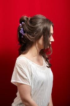 Portret van een jonge vrouw met lang golvend bruin haar in witte blouse op rood