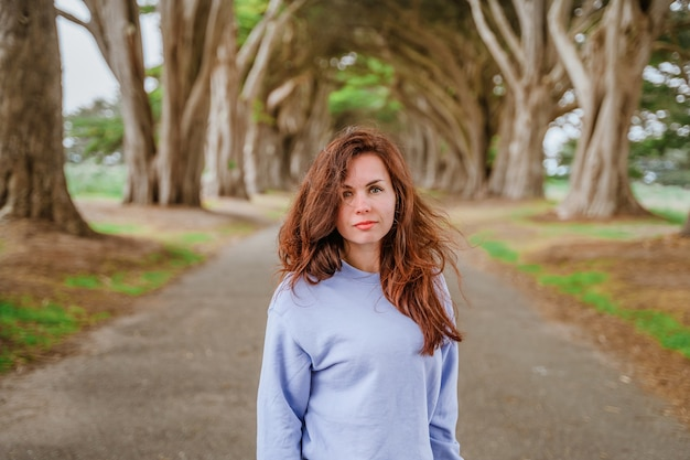 Portret van een jonge vrouw met lang haar in een cipresboomtunnel