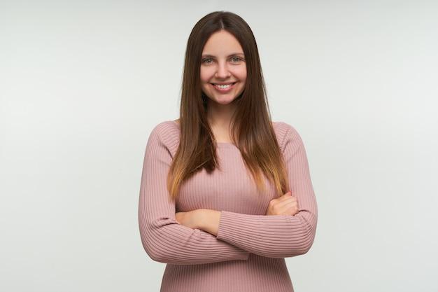 Portret van een jonge vrouw met lang haar naar beneden, staat met gekruiste handen