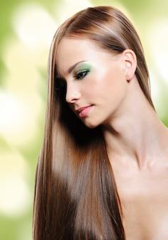 Portret van een jonge vrouw met lang steil haar. knipperende achtergrond. bokeh
