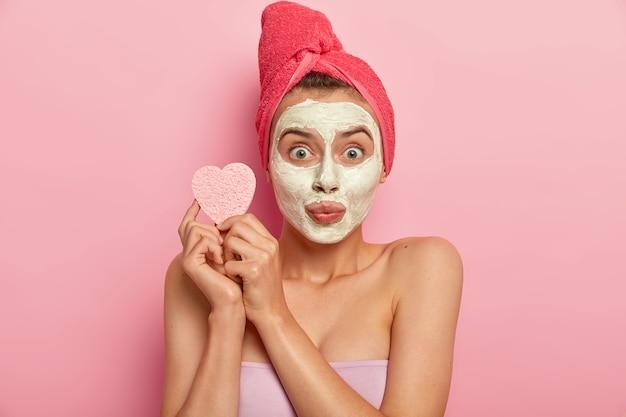 Portret van een jonge vrouw met mineraal natuurlijk masker op gezicht, heeft dagelijkse huidverzorging, houdt cosmetische spons voor het afvegen van de teint, zuivert de huid en verwijdert dode huidcellen, heeft een bad thuis