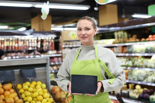 Portret van een jonge vrouw met minibord in winkel. eigenaar van een klein bedrijf