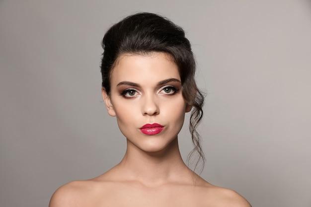 Portret van een jonge vrouw met mooie professionele make-up op grijs