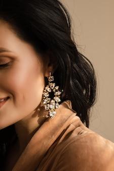 Portret van een jonge vrouw met oorbellen met edelstenen geïsoleerd