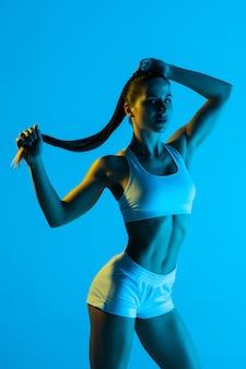 Portret van een jonge vrouw met paardenstaart geïsoleerd op een blauwe achtergrond
