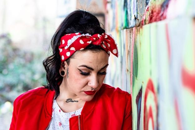 Portret van een jonge vrouw met piercings, dilataties en tatoeages gekleed in een rood jasje en een rode strik in haar haar. leunend tegen een graffitimuur.