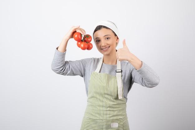 Portret van een jonge vrouw met rode tomaten over een witte muur Gratis Foto