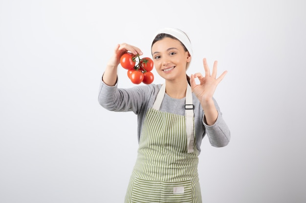 Portret van een jonge vrouw met rode tomaten over een witte muur