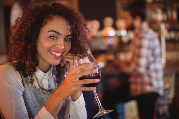 Portret van een jonge vrouw met rode wijn