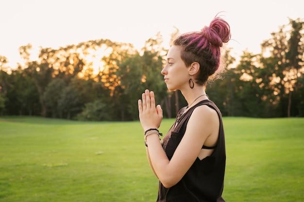 Portret van een jonge vrouw met roze dreadlocks die buiten yoga doet en mediteert in het park bij zonsondergang. vrijheid en energieconcept