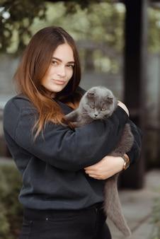 Portret van een jonge vrouw met schattige britse korthaar kat met bruine ogen. aanbiddelijk binnenlands huisdierconcept