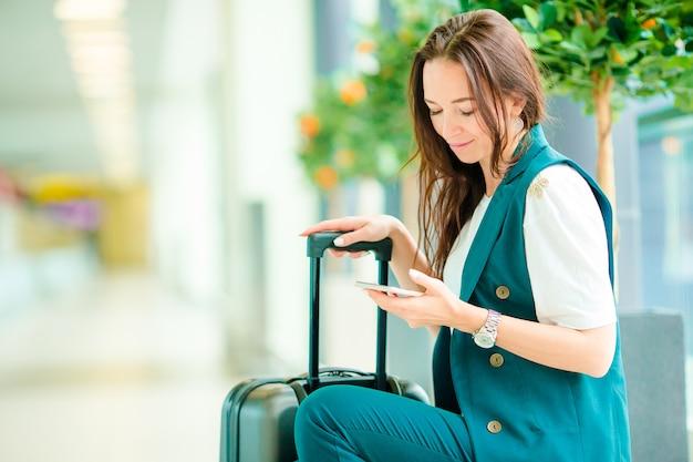 Portret van een jonge vrouw met smartphone in internationale luchthaven. luchtvaartlijnpassagier in een luchthavenzitkamer die op vluchtvliegtuigen wachten