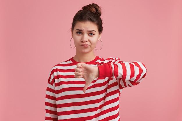 Portret van een jonge vrouw met sproeten, draagt een gestreepte longsleeve, kijkt met ongenoegen, is humeurig, mokkend en toont duimen naar beneden van afkeer.