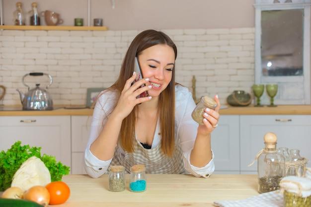 Portret van een jonge vrouw met verschillende kruiden in de keuken