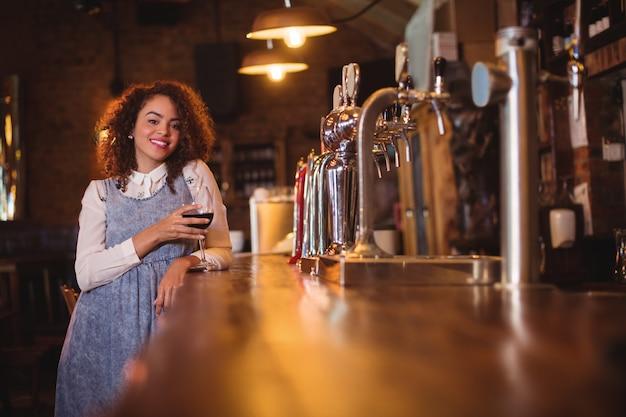 Portret van een jonge vrouw met wijn aan balie