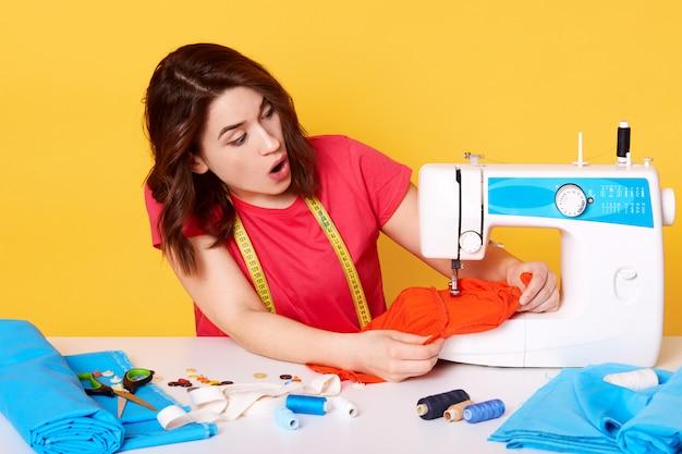 Portret van een jonge vrouw naaister zitten aan witte tafel en het maken van kleding op haar werkplek.